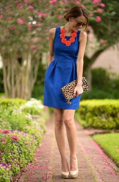 cobalt blue sleeveless collared waist dress with leopard print clutch bag