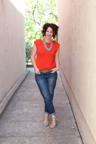 orange sleeveless blouse with cuffed jeans and brown belt