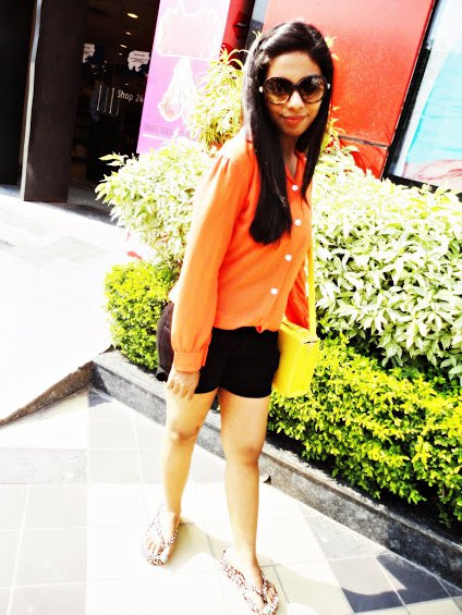 orange button up shirt with black mini shorts
