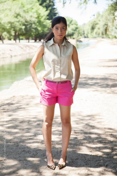 sleeveless ivory button-up shirt with hot pink mini shorts