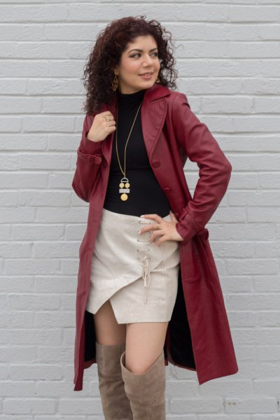 brown leather trench coat with black sweater and pink skirt