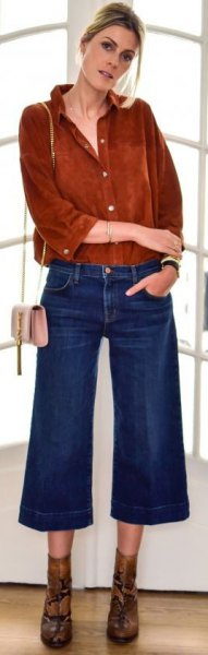 brown button up suede shirt with blue cut out cropped jeans