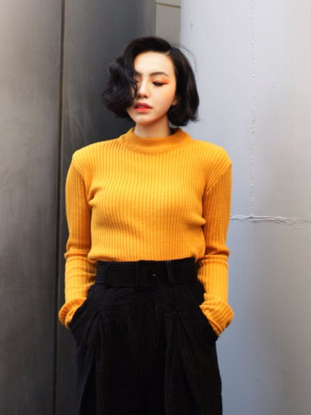 ribbed yellow sweater with black wide legged trousers