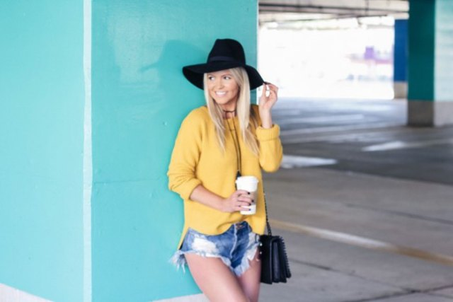 yellow sweater with blue ripped denim mini shorts and floppy hat
