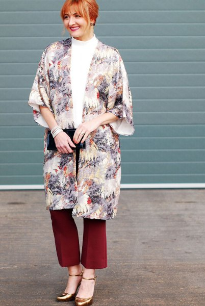 flora printed long cape with red flared pants and bronze heels