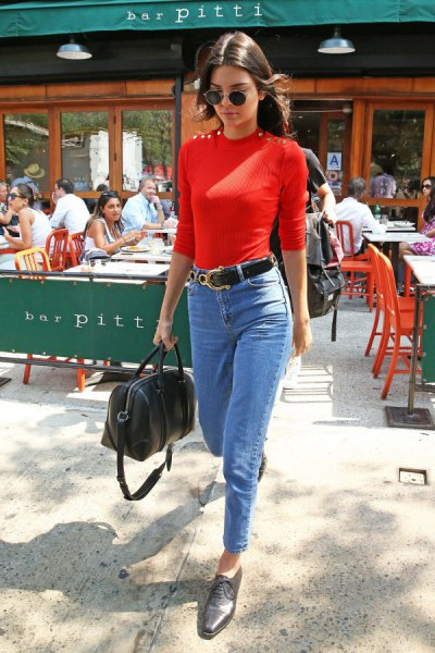 red sweater with red shape with light blue skinny ankle jeans