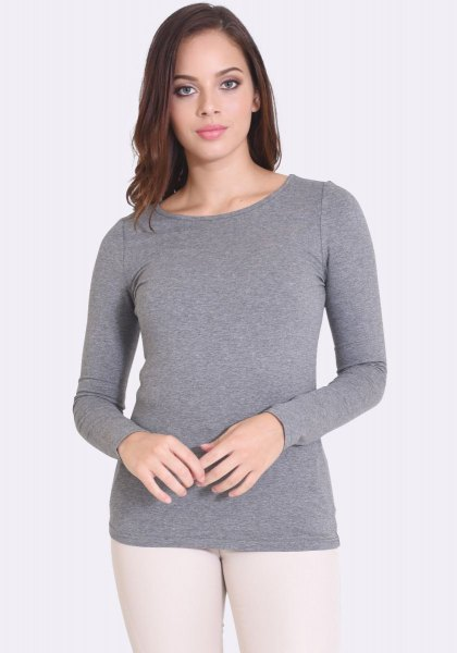 gray form fitting long sleeve top with white skinny jeans