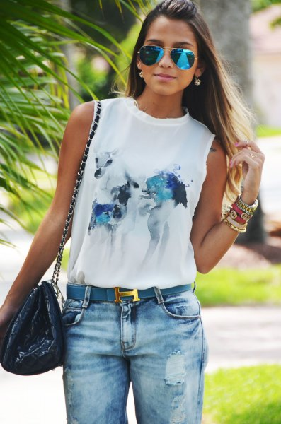 white sleeveless print tee with blue belt and jeans