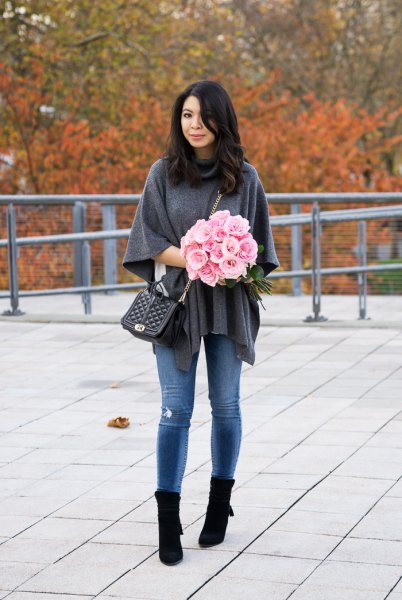 gray poncho shirt with blue skinny jeans and black boots