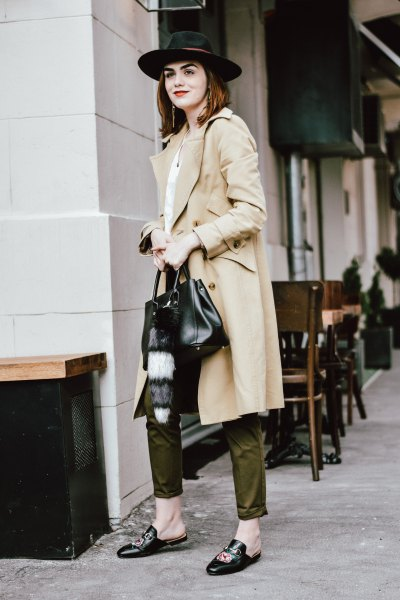 long beige trench coat with green pants and felt hat