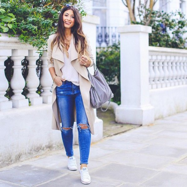 beige trench coat with ripped jeans and sneakers