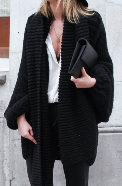 black chunky knitted cardigan with white blouse and leather clutch bag
