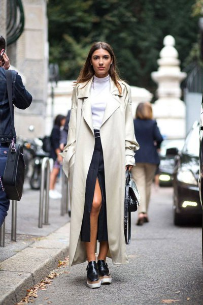 ivory maxi trench coat with white sweater with hair loss and black high split skirt