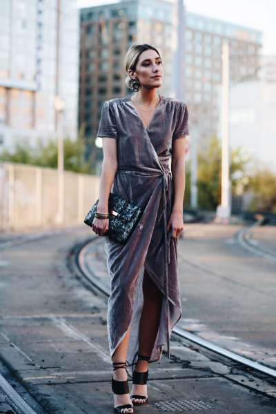 gray dress with high maxi with black clutch bag