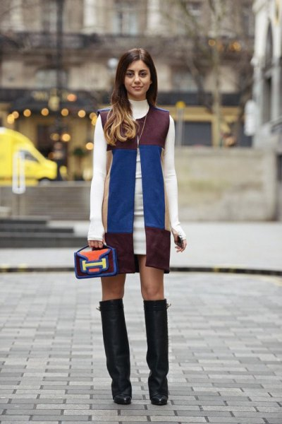 white sweater dress with black and blue sleeveless leather jacket