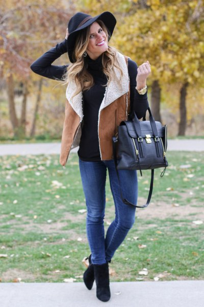 black mock neck sweater with shearling vest of camel and blue jeans