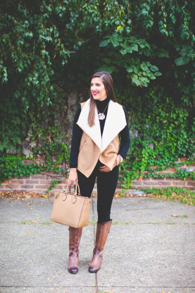 camel and white shearling vest with black skinny jeans and knee-high boots