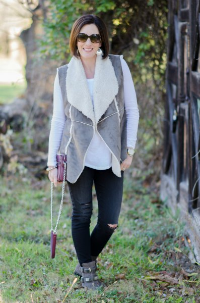 gray vest with black ripped jeans and suede ankle boots