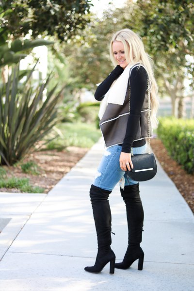 black shearling leather vest with denim shorts and high thigh boots