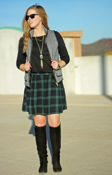 black long sleeve tee with green plaid skirt and gray vest