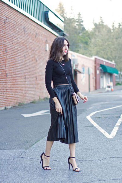 form-fitting cropped sweater with black midi-pleated skirt