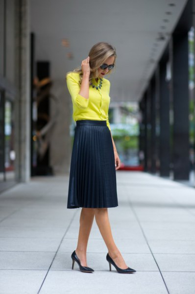 yellow blouse with black high waist pleated midi skirt