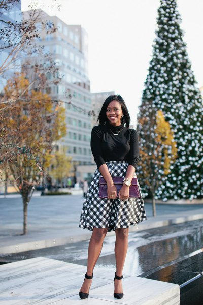 black half-warm knitted sweater with plaid midi-flared skirt