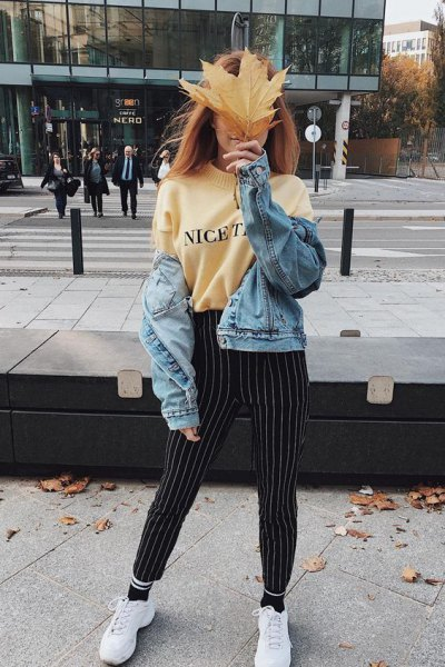 light yellow printed sweater with black and white striped pants