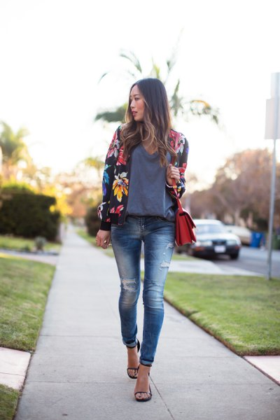 black floral bomber jacket with gray sweater and ripped skinny jeans
