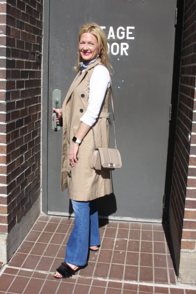 camel sleeveless coat with blue puffed jeans