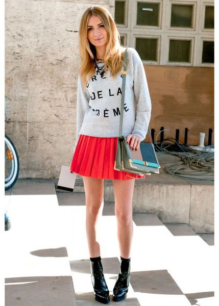 gray printed sweater with crew neck with orange pleated mini skirt