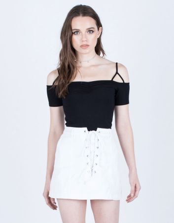 black cold shoulder top with white lace up denim skirt