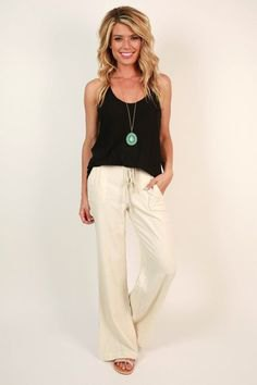 black top with white flared linen trousers