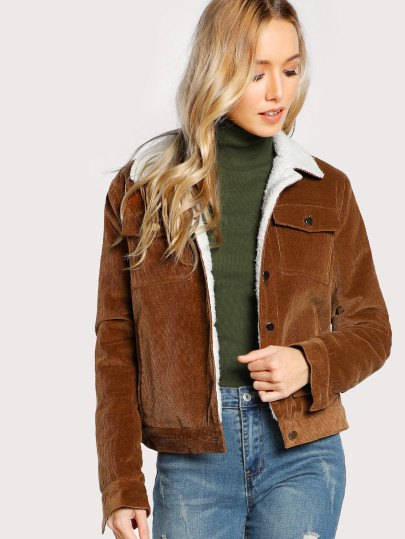brown sherpa lined jacket with green sweater neck and jeans