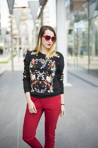 black embroidered sweater with red jeans