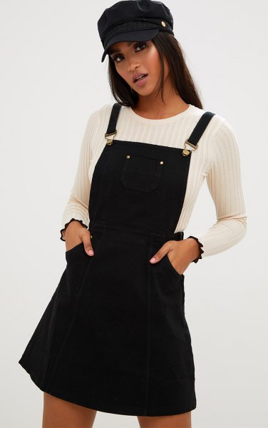 black denim pinafore dress with white ribbed sweater flat cap