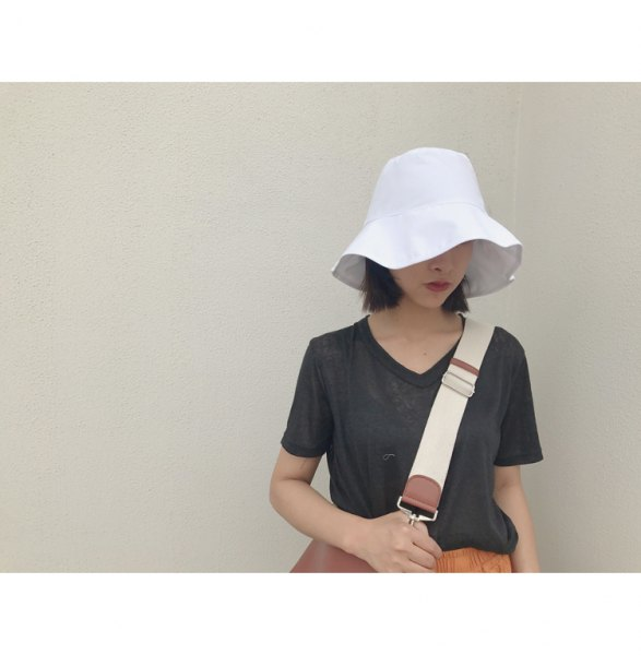 white bucket hat with dark gray tee orange midi skirt