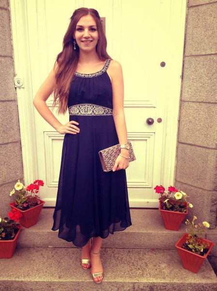 navy blue waist flared dress with silver evening clutch bag