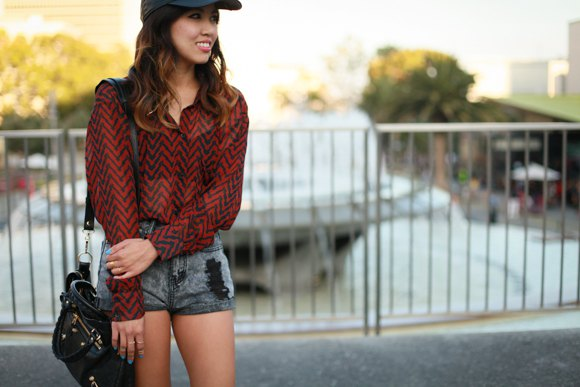baseball cap with red and black patterned shirt gray denim shorts