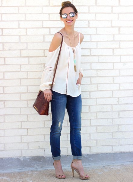 white cold shoulder sweater with cuffed skinny jeans
