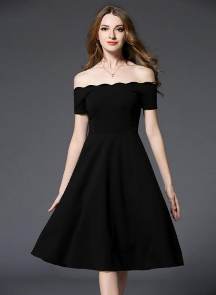 scallop at the bottom of the black dress of the shoulders