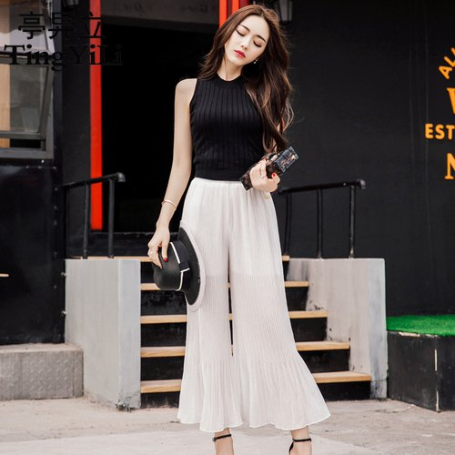 black sleeveless knitted sweaters white pants