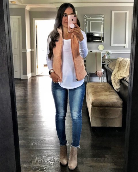 cream vest over white jeans