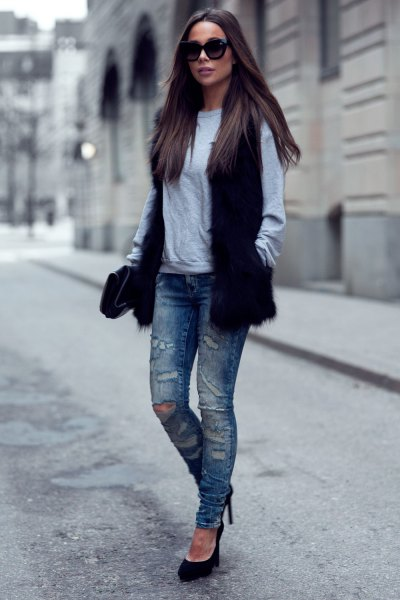 black fur vest with gray sweater and ripped slim fit jeans