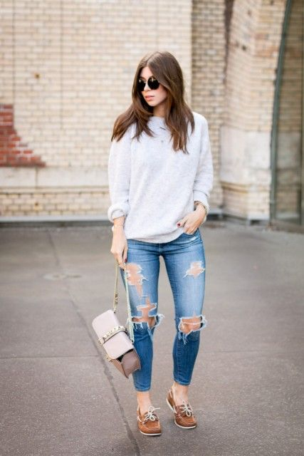 With loose sweatshirt, distressed jeans and small bag .