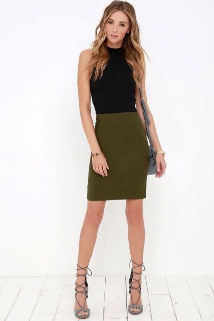 Outfit with olive green skirt, black shirt and lace up heels .