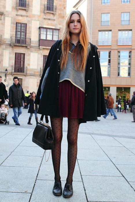 Black polka dot pantyhose and black cape over burgundy dress (con .